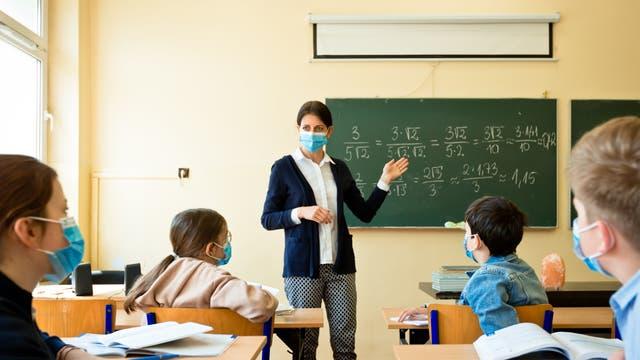 Lehrerin und ihre Klasse mit Masken im Klassenraum