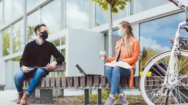 Zwei Menschen auf einer Parkbank mit Abstand und Maske.