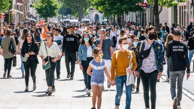 Eine Menschenmenge in einer Einkaufsstraße, zum Teil mit, zum Teil ohne Maske. Aufgenommen in Frankreich nach dem Ende des Lockdowns.