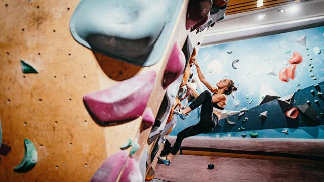 Eine Sportlerin erklimmt eine Kletterwand.