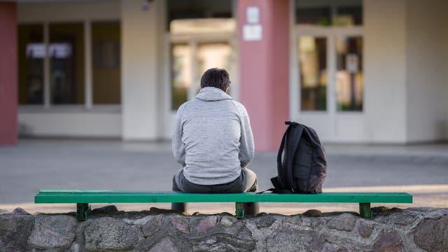 Ein Jugendlicher sitzt auf einer Bank auf dem Schulhof. (Symbolbild)