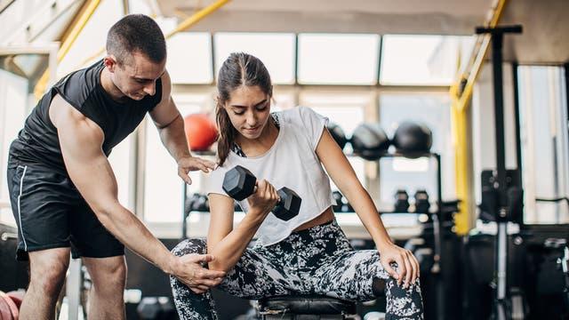 Frau beim Krafttraining mit Hantel, begleitet von einem Fitnesstrainer