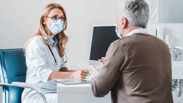Ein Patient spricht mit seiner Ärztin.