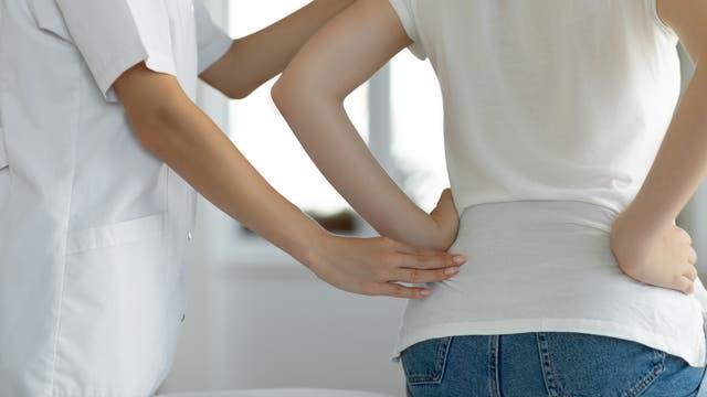 Frau wird wegen Rückenschmerzen behandelt (Symbolbild)