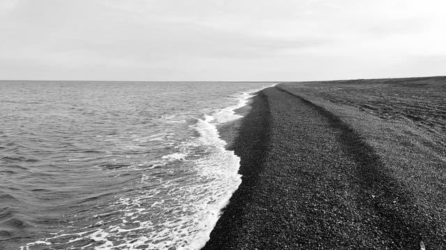 Ein schnurgerader Strandsaum aus dunklem Geröll zieht sich Richtung Horizont.