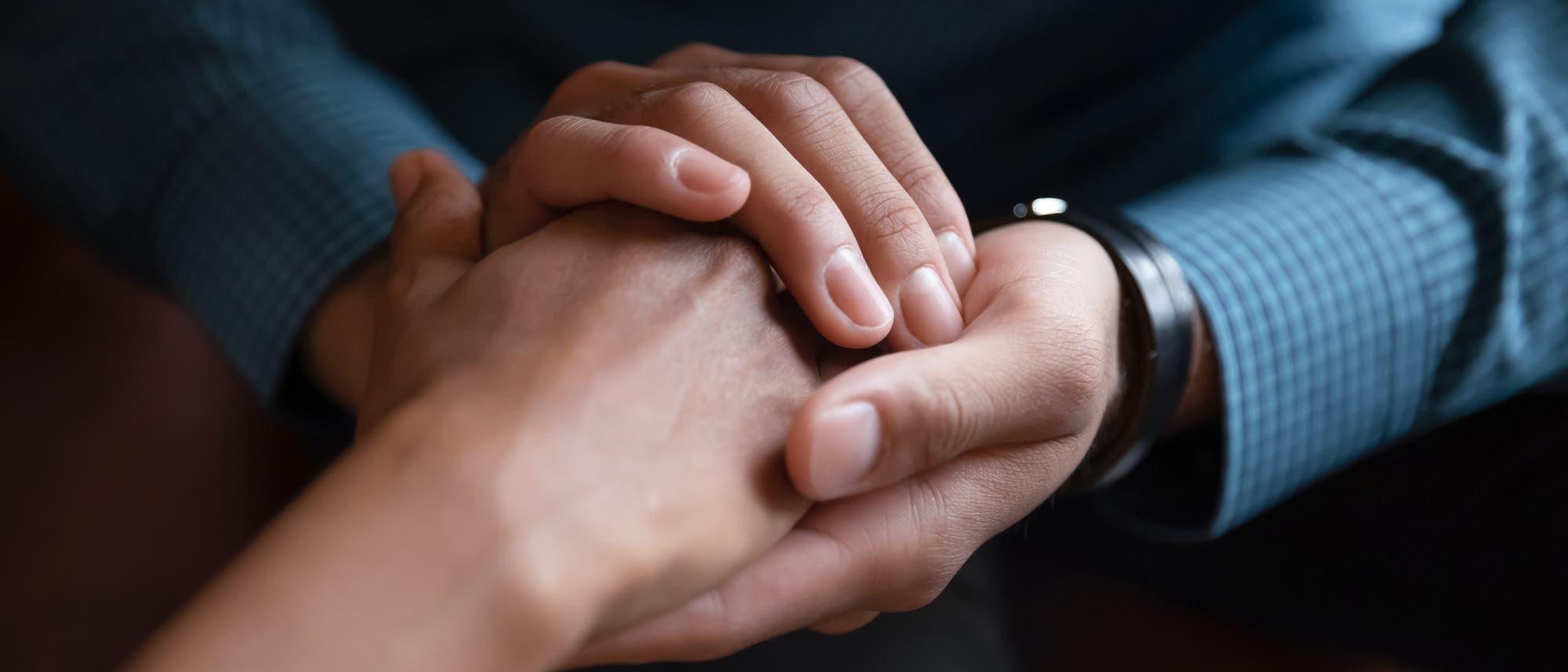 Zwei Hände halten tröstend zwei andere Hände