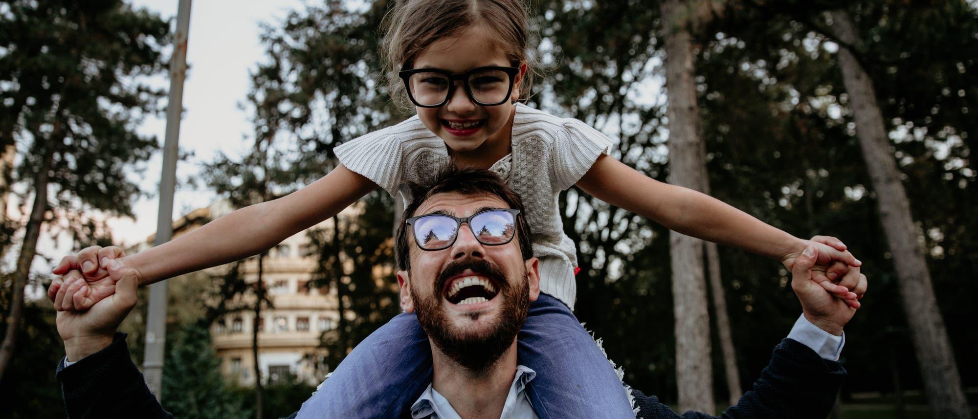 Kleines Mädchen sitzt strahlend auf den Schultern des lachenden Vaters