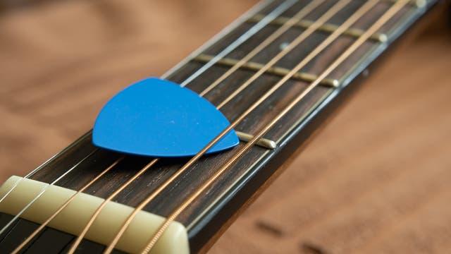 Gitarrenhals mit blauem Plektrum auf den Saiten.