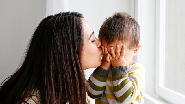 Mutter gibt weinendem Kind ein Küsschen
