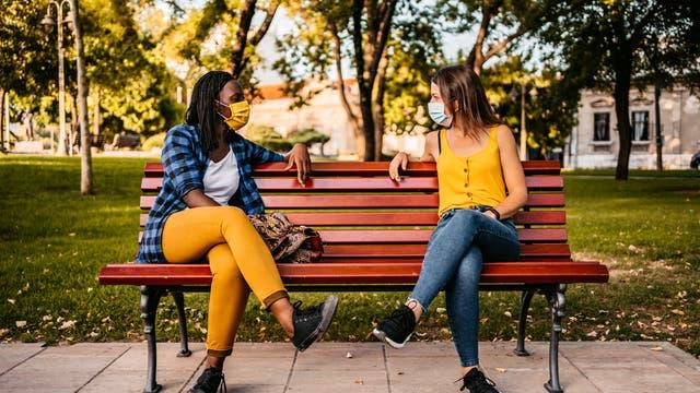 Zwei Frauen unterhalten sich auf einer Parkbank