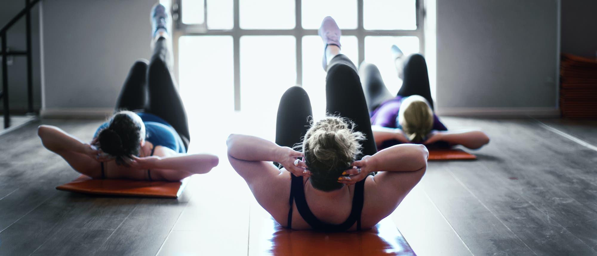 Drei Frauen machen Fitnessübungen in einem Trainingsraum