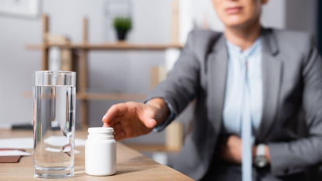 Frau im Büro hält sich den Bauch und greift nach Tabletten