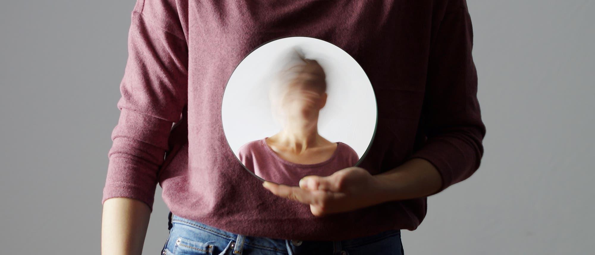 Frau hält einen Spiegel mit ihrem eigenen verwaschenen Abbild
