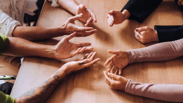 Hände von mehreren Personen, teils in ähnlicher Haltung