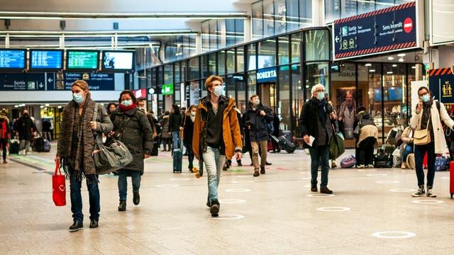 Menschen in einem Pariser Bahnhof, mit Masken vorm Gesicht