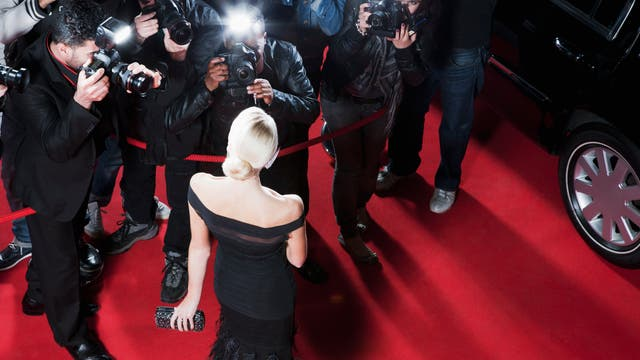 Elegante Blondine mit Glitzertäschchen umringt von Fotografen auf dem roten Teppich
