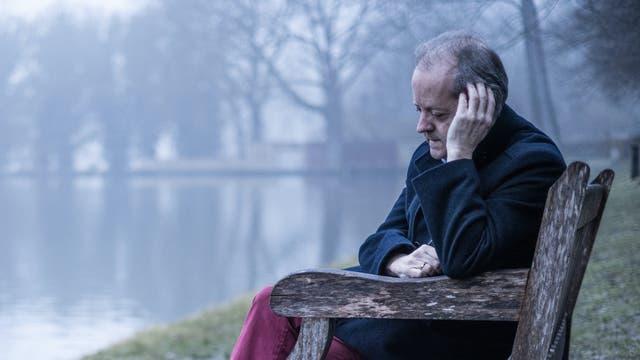 Ein Mann mit grauem Haar sitzt nach nachdenklich auf einer Bank am See