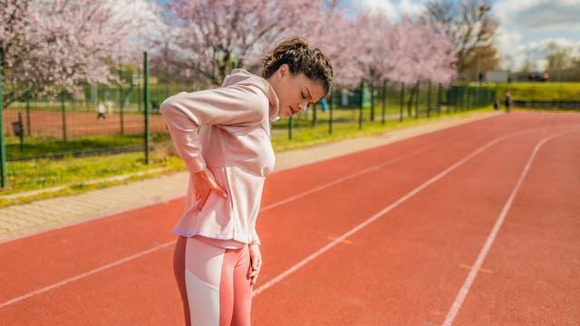 Junge Sportlerin greift sich an den Rücken