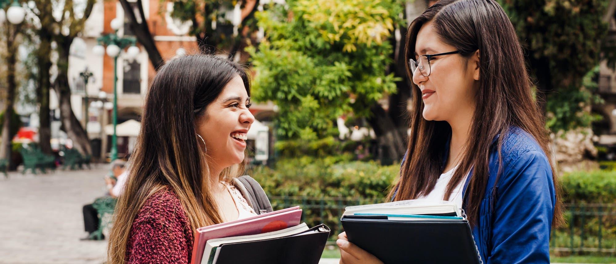 Zwei Studentinnen unterhalten sich auf dem Campus