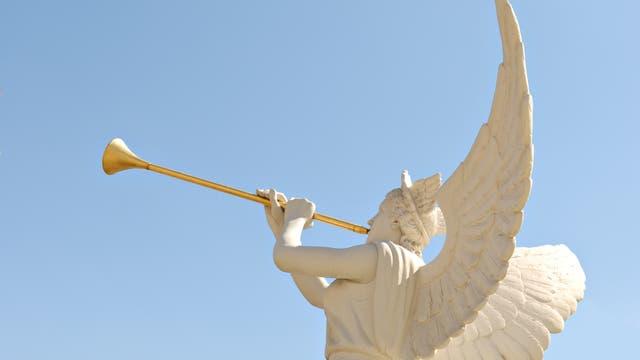 Eine Engelsstatue mit goldener Trompete gegen blauen Himmel fotografiert.