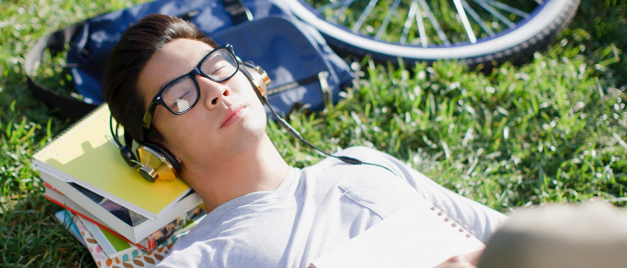 Mann mit Kopfhörern döst auf dem Rasen