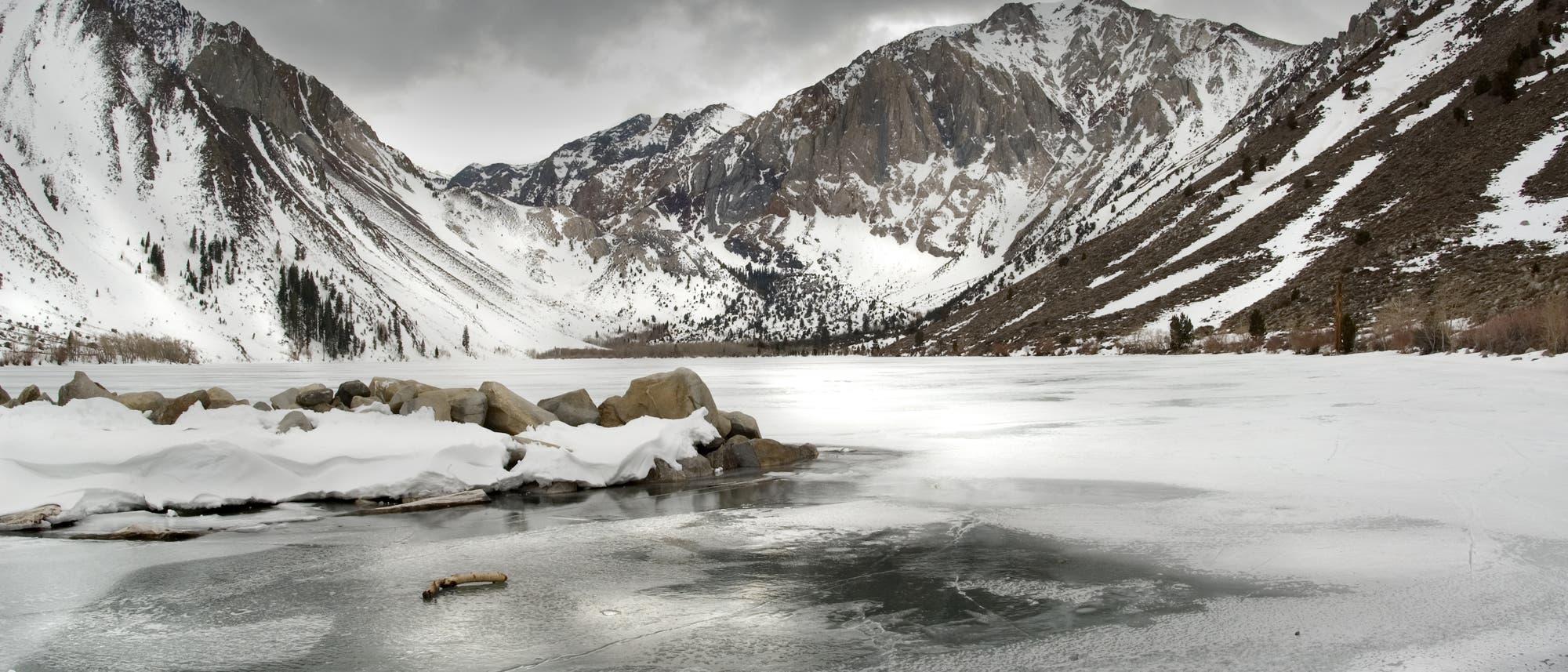 Vereister See vor schneebedeckten Bergen
