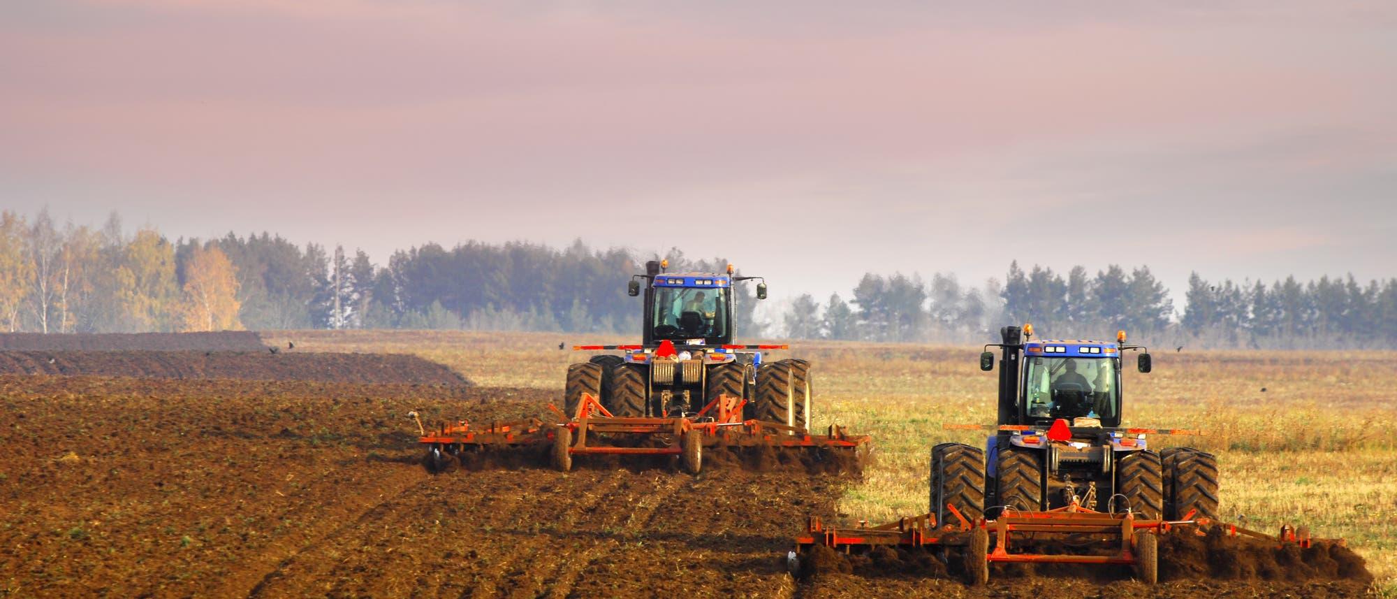 Traktoren eggen einen Acker