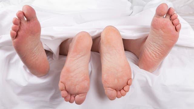 Seniorenfüße unter dem Bettlaken
