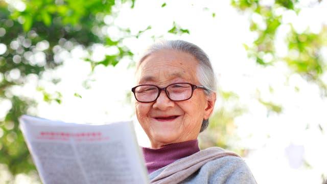 Ältere Dame liest hochvergnügt Zeitung.