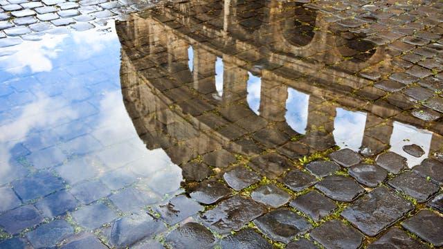 Das Kolosseum spiegelt sich malerisch in einer Wasserpfütze auf Kopfsteinpflaster