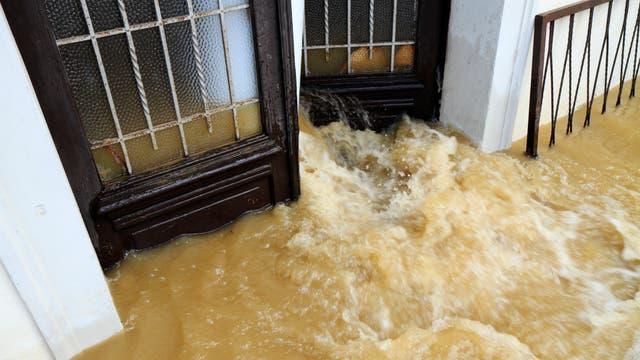 Schlammiges Wasser strömt durch eine Tür.