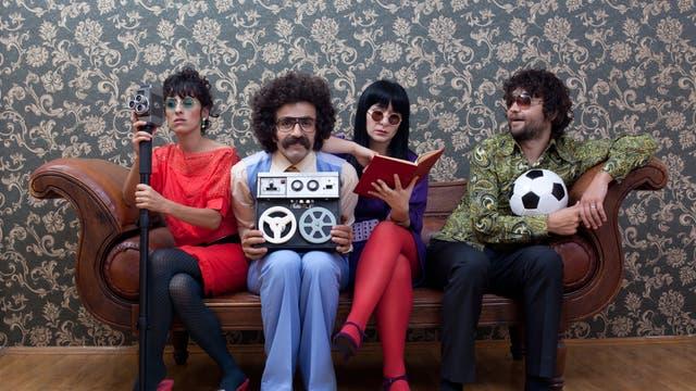 Vier freakige junge Leute im Sixties- oder Seventies-Outfit auf einer Couch