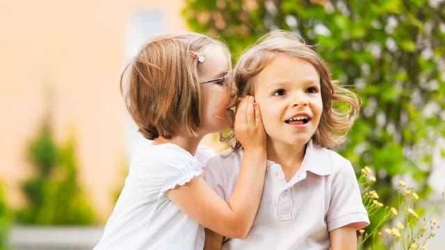 Ein kleines Mädchen flüstert einem anderen etwas ins Ohr.