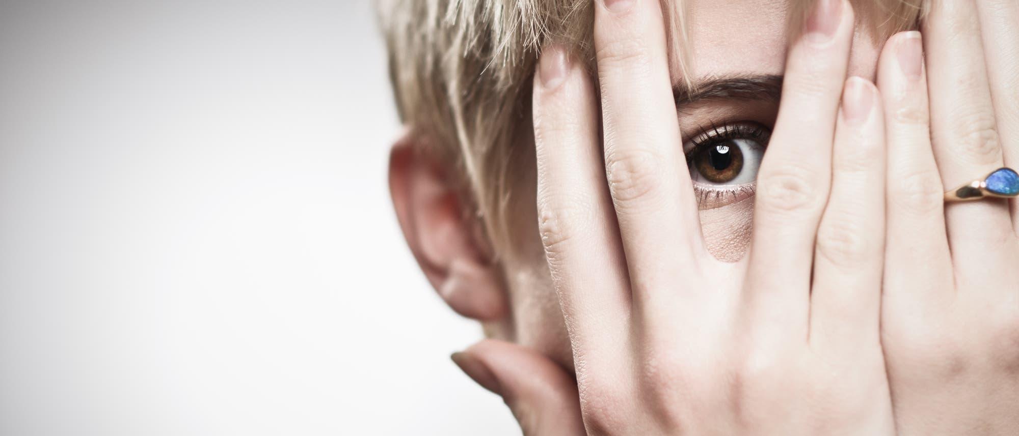 Frau verdeckt Gesicht mit Händen