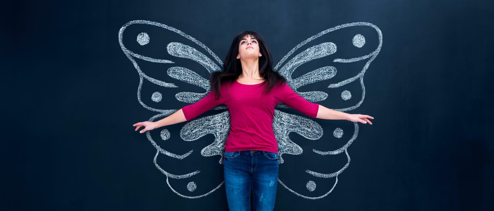 Eine Frau steht mit ausgebreiteten Armen vor auf eine Tafel gezeichneten Schmetterlingsflügeln