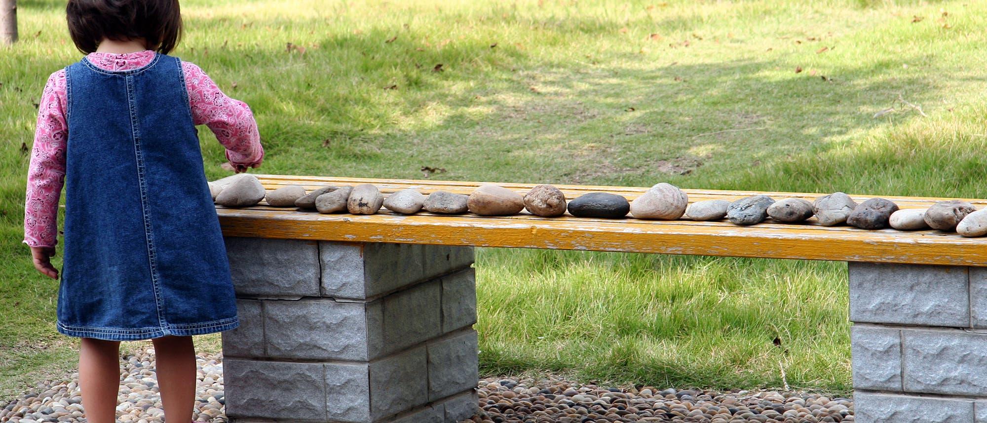 Kind ordnet Steine auf einer Bank der Reihe nach