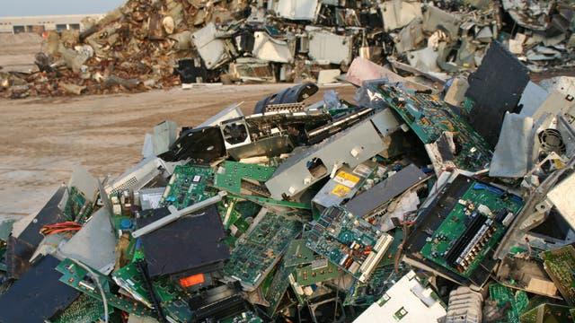 Ein ungeordneter Haufen aus Computerteilen liegt auf nackter Erde.