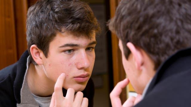 Jugendlicher prüft Akne im Spiegel