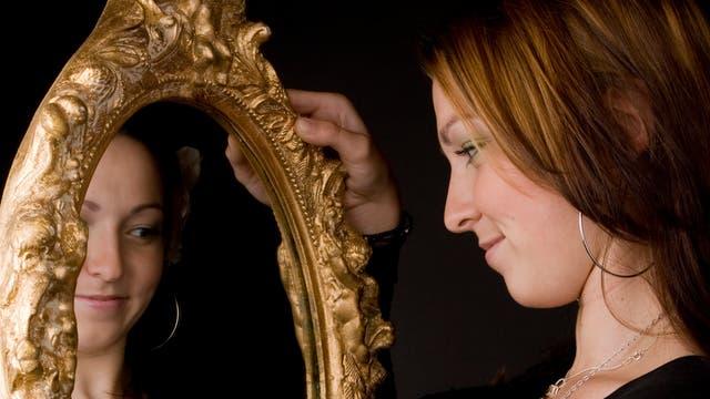 Eine Frau blickt glücklich in einen Spiegel.