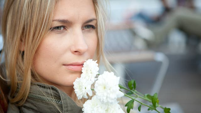 Frau hält sich Blumen ans Gesicht