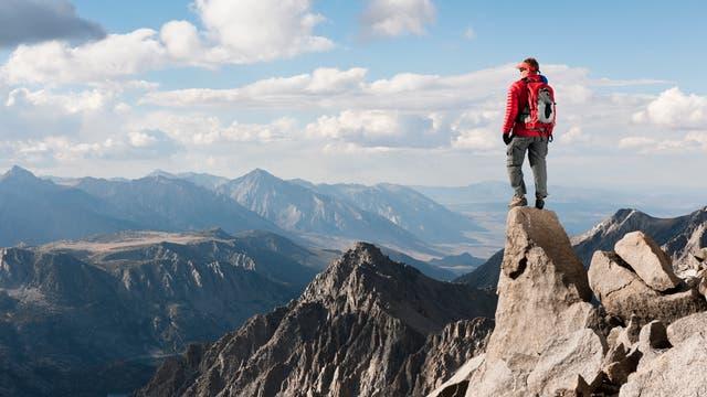 Ein Mann blickt von einem Berggipfel auf die umliegenden Berge