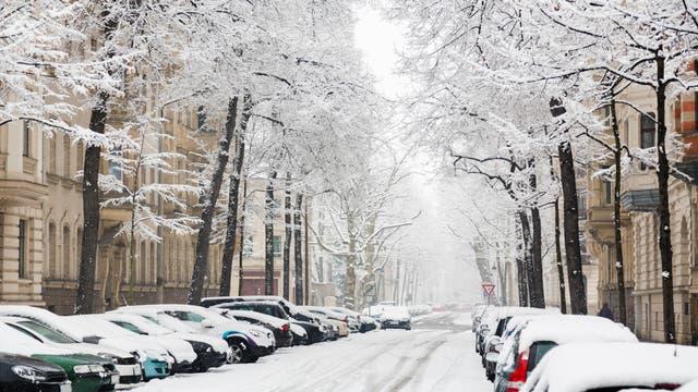 Eine verschneite Straße samt schneebedeckten Autos zwischen hübschen Altbauten.