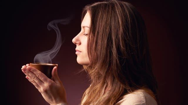Frau mit duftender Tasse Kaffee in der Hand