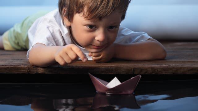 Ein kleiner Junge spielt mit einem Papierboot im Wasser