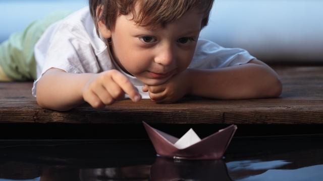 Ein kleiner Junge lenkt ein Papierboot im Wasser
