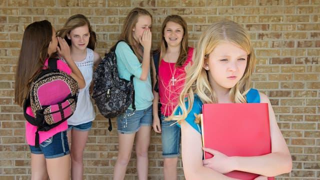 Mädchen tuscheln über Mitschülerin: Sexuelle Gewalt kann auch auf verbaler Ebene stattfinden