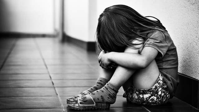 Ein Kind kauert in einem gefliesten Gang an der Wand.