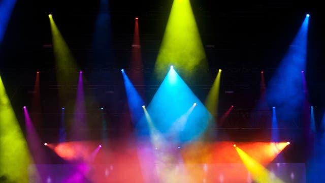 Scheinwerfer werfen farbige Lichtkegel unterschiedlicher Größe in einen dunklen Raum