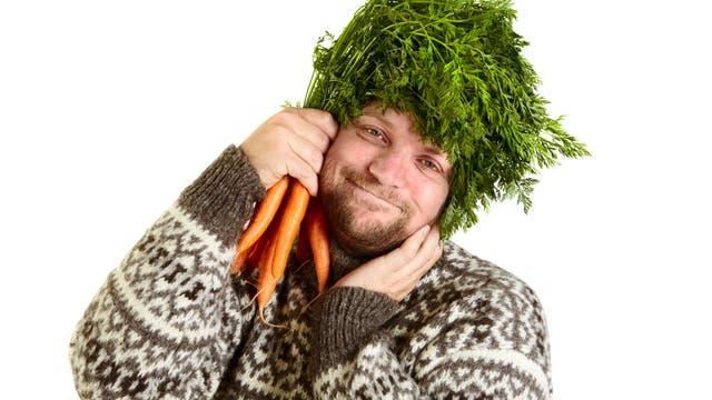Ein diätaffiner Mann posiert mit Gemüse