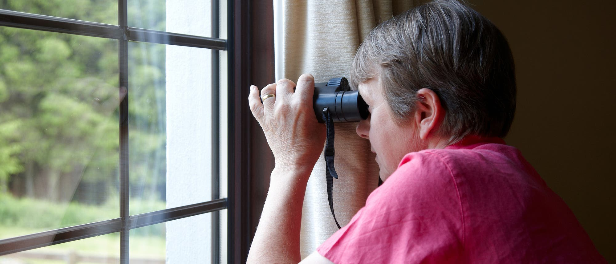 Frau schaut mit dem Fernglas aus dem Fenster